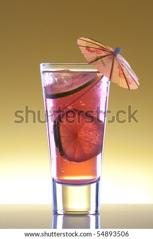 Cool, fresh, red cocktail with lime on a yellow background - stock photo