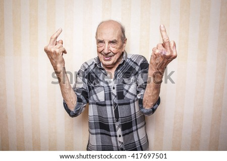 cool funny elder man making middle finger sign - stock photo