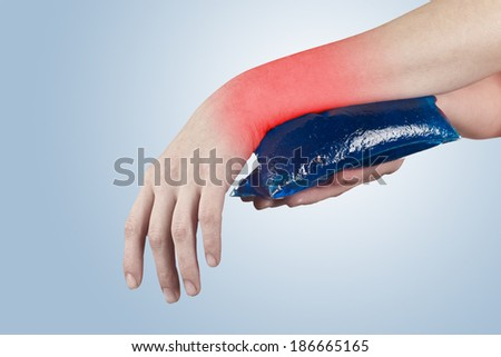 Cool gel pack on a swollen hurting wrist. Medical concept photo.  - stock photo