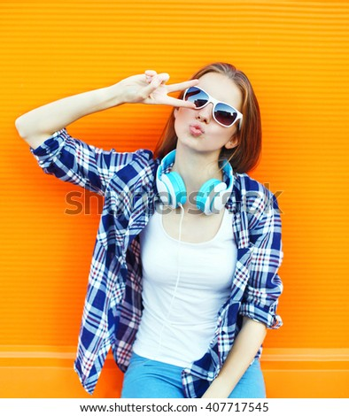 Cool girl having fun listens music in headphones over colorful background - stock photo