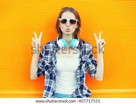 Cool girl having fun listens music over colorful background - stock photo