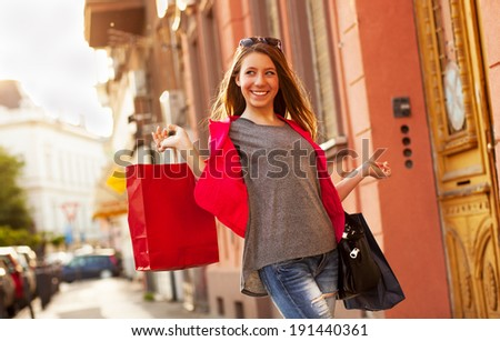 Cool girl walking on the street with shopping bags - stock photo