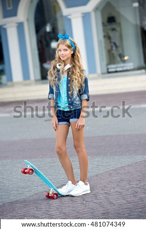 Cool girl wearing a blue clothes, headphones and skateboard in city