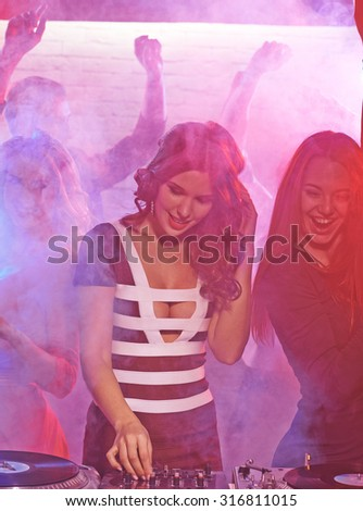 Cool girl with headphones standing by deejay equipment among company of friends