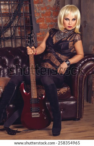 Cool glam rock blonde sexy woman in black lingerie with red guitar sitting on a brick wall urban background - stock photo