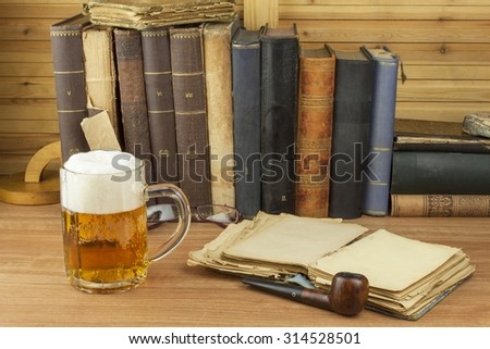 Cool glass of beer on the table. Relax with a good book with a glass of cold beer. The concept relax with a good beer. Pouring a glass of beer for readers of the book. Alcohol and study. - stock photo