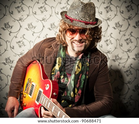 Cool guitar player after performance - stock photo