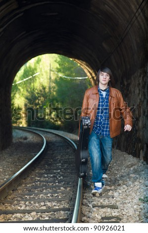 Cool guitarist portrayed inside a railway tunnel - stock photo