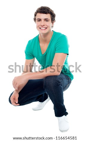 Cool guy wearing white sneakers, squatting posture. Looking at camera - stock photo