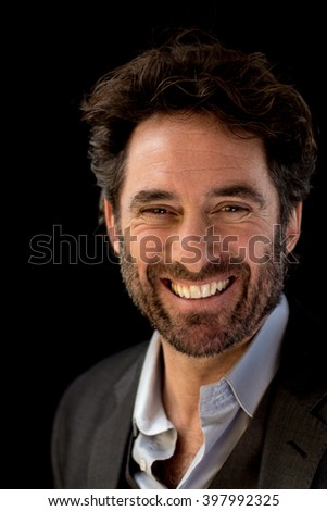 Cool guy with beard smiling on black background