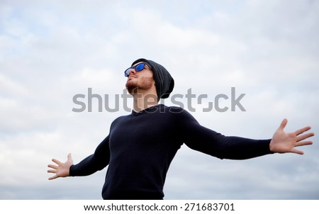 Cool handsome guy with his arms extended with the sky of background - stock photo