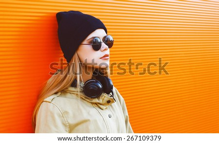 Cool hipster girl wearing a black hat and headphones listens to music enjoys freedom against a colorful wall in the city, street fashion concept - stock photo