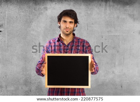 cool indian man holding a blackboard - stock photo