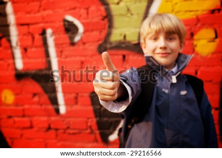 Cool kid standing in front of a graffiti wall. Focus in hand