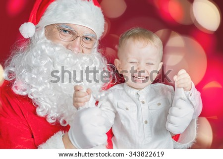 Cool little boy and Santa Claus at Christmas holiday. Concept of traditional world celebration, family holiday. New Year. Your dad dressed in a Santa Claus costume!