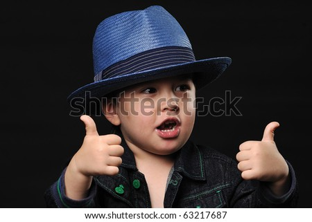Cool little boy in a fancy hat showing thumbs up - stock photo