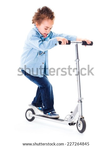 Cool little boy in jeans, playing with scooter - stock photo