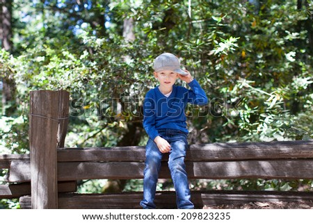 cool little boy sitting on the fence