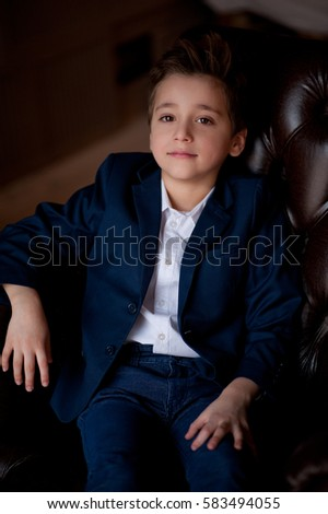 Cool little boy wearing a jacket in the studio in business style