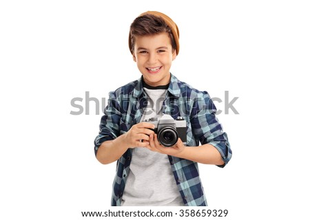 Cool little boy with a brown hat and checkered shirt holding a camera and smiling isolated on white background - stock photo