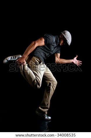 Cool looking dancer jumping on black background - stock photo