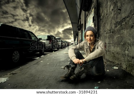 cool looking girl sitting on a city street - stock photo