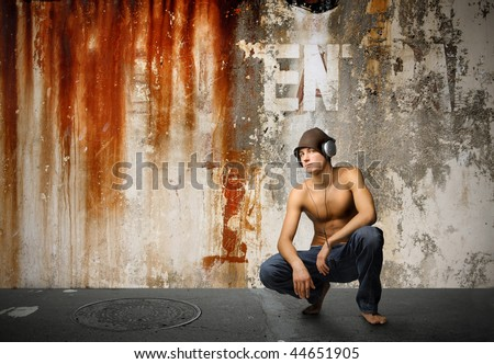 cool looking guy listening music with grunge wall on the background - stock photo
