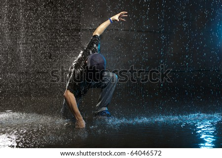 Cool looking hip-hop dancer in aqua studio - stock photo