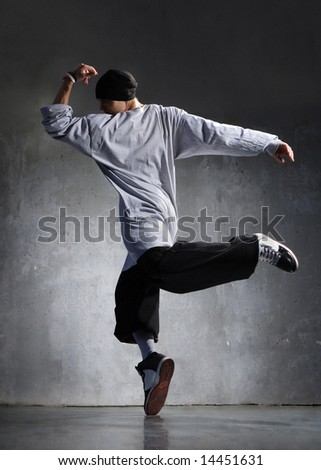 cool looking hip-hop dancer posing on old wall - stock photo