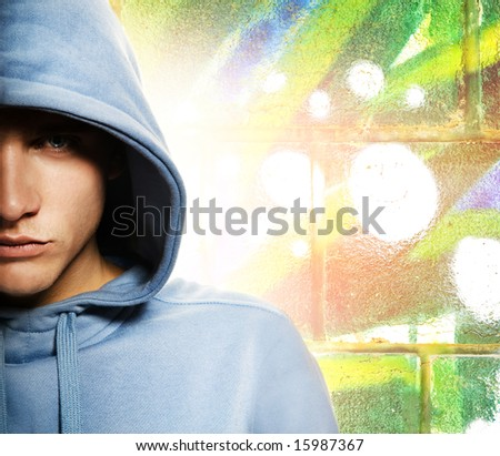 Cool looking man in a hood over abstract graffiti background - stock photo