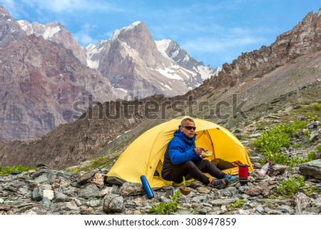 Cool man eating lunch in mountain hike. Climber sitting in yellow single tent set up on rocky terrain with camping stove plate bread mug eat cooked lunch high mountains and blue sky background - stock photo