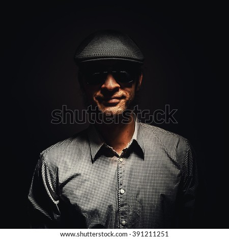 Cool man in good mood, wearing a hat and sun glasses.