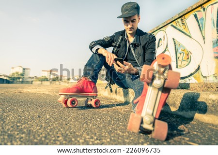Cool man with roller skating shoe using his mobile phone - Concepts of youth,sport,lifestyle and 80s vintage style - stock photo