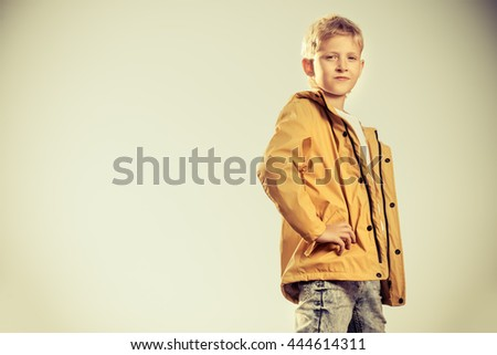 Cool modern eight-year boy posing on a sky background. Kid's fashion.