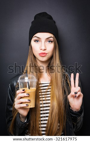 Cool modern teenage girl with long blonde hair, wearing striped shirt, black leather jacket, black beanie hat gesturing peace holding a cup of takeaway coffee. Black background, vertical, retouched. - stock photo