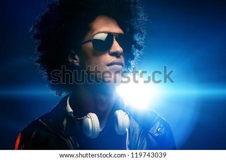 Cool nightclub party dj portrait with headphones lighting flare and sunglasses - stock photo