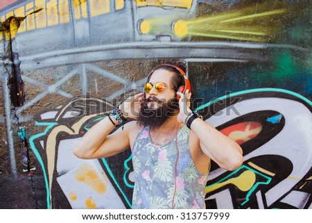 Cool portrait of trendy hipster man,listening music on big earphones,round sunglasses,mirrored glasses,mans fashion look,accessory,trendy man,autumn vintage colors,deep house,electro pop,music - stock photo