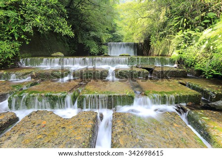 Cool refreshing cascades in a mysterious forest with sunlight shining through the lavish greenery ~ A spring scenery of Taiwan - stock photo
