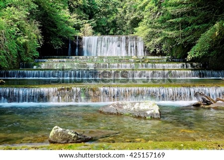 Cool refreshing cascades in a mysterious forest with sunlight shining through the lavish greenery ~ Beautiful scenery of river and waterfall of Taiwan in springtime - stock photo
