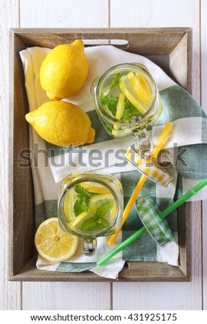 Cool refreshing drink: water, lemon and mint on a wooden tray - stock photo