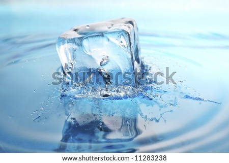 cool refreshing ice-cube dropped into freshly poured water. splashes frozen in time. - stock photo