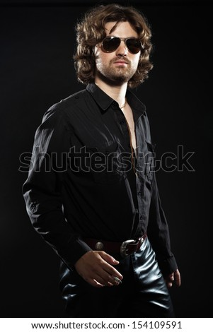 Cool rock style dancing musician with long brown hair and beard. Dressed in black. Wearing sunglasses. - stock photo