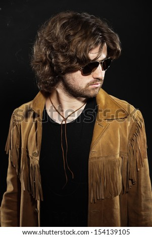 Cool rock style musician with long brown hair and beard. Wearing sunglasses. - stock photo