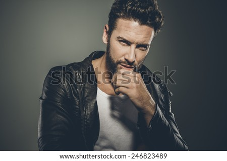 Cool seductive man in black leather jacket flirting and looking at camera - stock photo