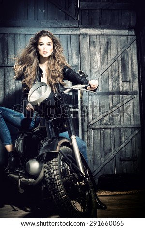 Cool sensual biker girl in black leather jacket and blue jeans sitting on old fashioned motorcycle in garage interior on grey wooden wall background, vertical picture - stock photo
