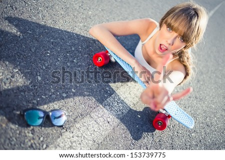 Cool skater girl doing rock and roll hand gesture lying on her board on a road - stock photo