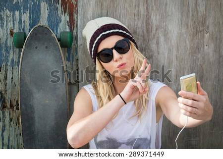 Cool skater girl taking selfie - stock photo