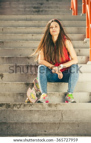 Cool skater young long haired girl with skateboard sitting on the urban stairs. Active lifestyle funky in summer. Outdoor trendy sport teenage.