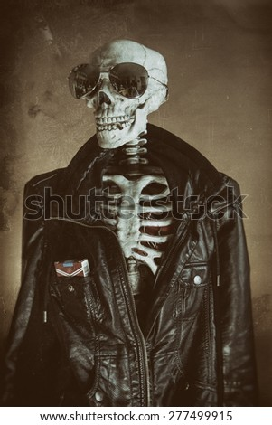 Cool Skeleton Vintage. A cool skeleton wearing a leather jacket and sunglasses, with cigarettes in his pocket and a smoke in his mouth. His heart visible in his ribcage. Edited in vintage film style. - stock photo