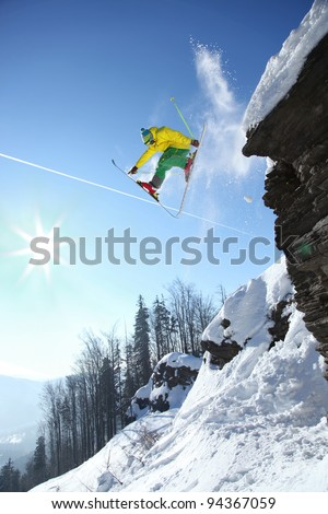 Cool skier jumping against blue sky